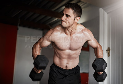 Buy stock photo Cropped shot of a handsome and muscular young man working out with dumbbells in the gym