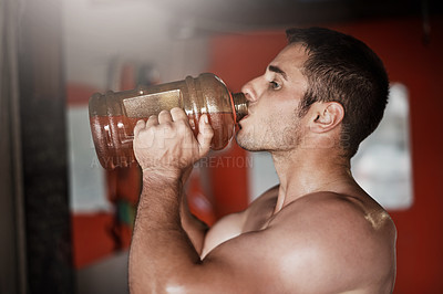 Buy stock photo Cropped shot of a handsome and muscular young man drinking pre workout in the gym