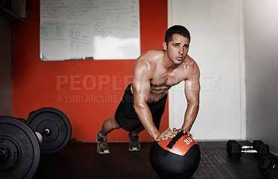 Buy stock photo Full length shot of a handsome and muscular young man working out with a medicine ball in the gym