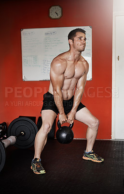 Buy stock photo Full length shot of a handsome and muscular young man working out with a kettle bell in the gym