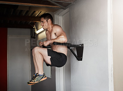 Buy stock photo Full length shot of a handsome and muscular young man working out on a dip bar in the gym