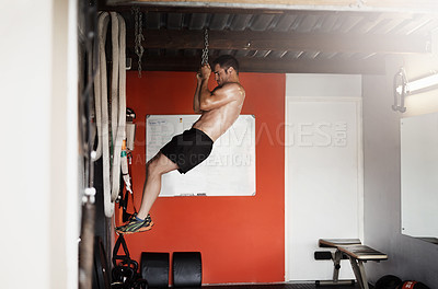 Buy stock photo Full length shot of a handsome and muscular young man doing pullups using a chain in the gym