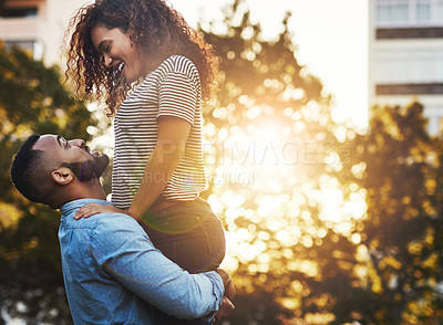 Buy stock photo Cropped shot of young handsome man lifting up his beautiful girlfriend outside in a public park