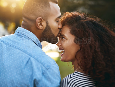 Buy stock photo Rearview shot of a young attractive couple spending time together outside in a public park