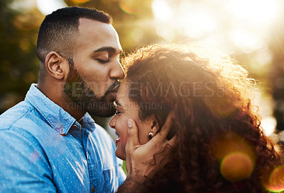 Buy stock photo Shot of a young man lovingly kissing his girlfriend in the park