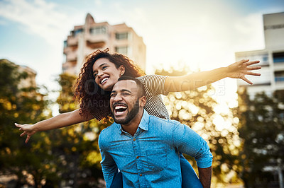 Buy stock photo Shot of a happy young couple enjoying a piggyback ride in the park