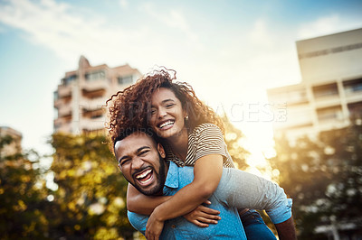 Buy stock photo Portrait of a happy young couple enjoying a piggyback ride in the park