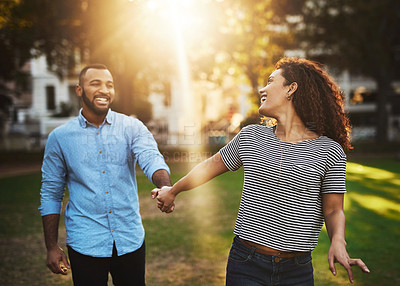 Buy stock photo Shot of a happy young couple holding hands in the park