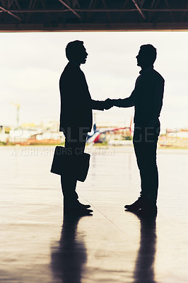 Buy stock photo Full length shot of two unrecognizable businessmen shaking hands while standing in a hanger at the airport