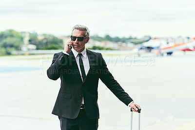 Buy stock photo Cropped shot of a handsome mature businessman walking with his luggage outside of the airport