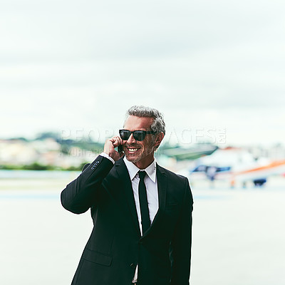 Buy stock photo Cropped shot of a handsome mature businessman talking on his cellphone while walking outside of the airport