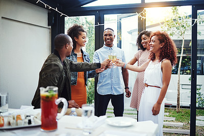 Buy stock photo Shot of a group of young friends making a toast