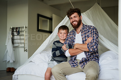 Buy stock photo Cropped portrait of a handsome young man and son sitting on the bed at home