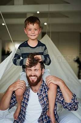 Buy stock photo Cropped portrait of an adorable little boy sitting on his dad's shoulders while sitting on the bed at home