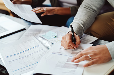 Buy stock photo Closeup shot of an unrecognizable couple going through paperwork together at home