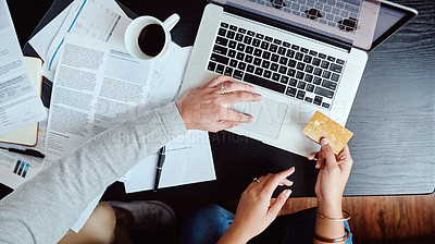 Buy stock photo High angle shot of an unrecognizable couple using a credit card and laptop at home