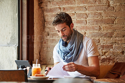Buy stock photo Cropped shot of a young man doing freelance work in a cafe