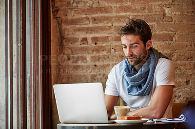 Buy stock photo Shot of a young man working on his laptop while sitting in a cafe