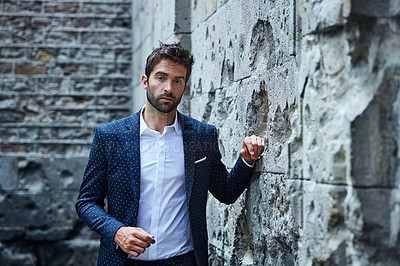Buy stock photo Cropped portrait of a handsome young businessman standing in an urban alleyway