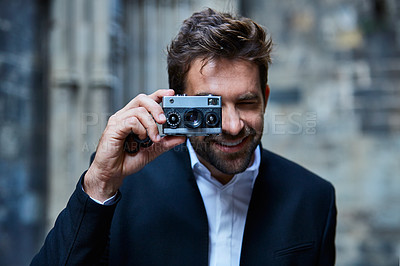 Buy stock photo Cropped shot of a handsome young businessman taking pictures while standing in an urban alleyway