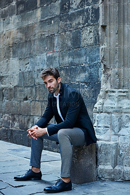 Buy stock photo Full length shot of a handsome young businessman sitting in an urban alleyway