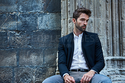 Buy stock photo Cropped shot of a handsome young businessman sitting in an urban alleyway