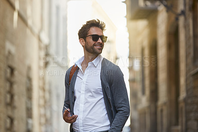 Buy stock photo Cropped shot of a handsome young businessman sending a text while walking through an urban alleyway