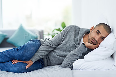 Buy stock photo Cropped portrait of a young man lying on his bed while feeling unwell at home