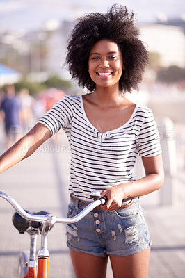Buy stock photo Portrait of a young beautiful woman walking with her bicycle on the promenade at the beach