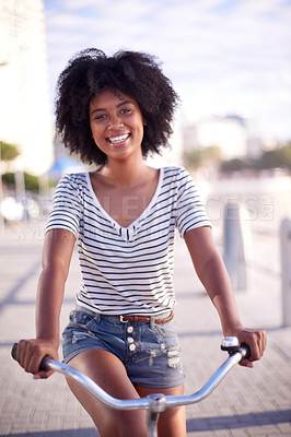 Buy stock photo Portrait of a young beautiful woman riding a bicycle on the promenade at the beach