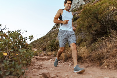 Buy stock photo Low angle shot of a handsome young man out for a run in the mountains
