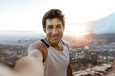 Buy stock photo Cropped portrait of a handsome young man taking a selfie while running in the mountains