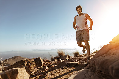 Buy stock photo Full length shot of a handsome young man out for a run in the mountains