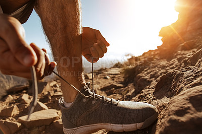 Buy stock photo Low angle shot of an unrecognizable young man tying his laces while out for a run in the mountains