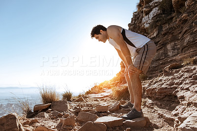 Buy stock photo Full length shot of a handsome young man looking tired while out for a run in the mountains