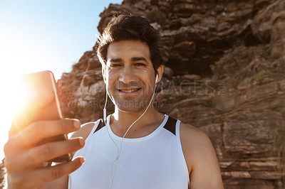 Buy stock photo Cropped portrait of a handsome young man listening to music while out for a run in the mountains