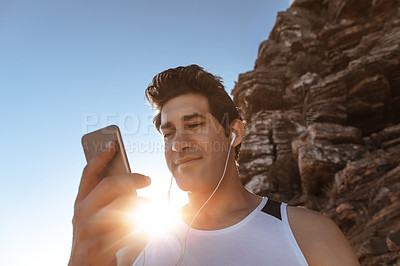Buy stock photo Low angle shot of a handsome young man listening to music while out for a run in the mountains