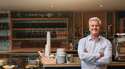 Buy stock photo Cropped portrait of a mature male entrepreneur standing with his arms crossed in his self-owned coffee shop