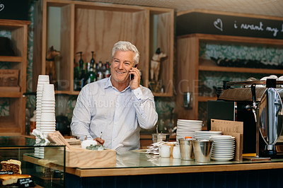 Buy stock photo Cropped shot of a mature male entrepreneur writing down telephonic orders while standing in his self-owned coffee shop
