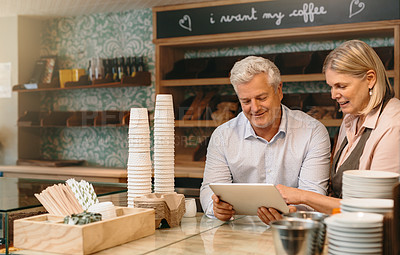 Buy stock photo Cropped shot of a mature couple working on a tablet while standing behind the counter of their self-owned coffee shop