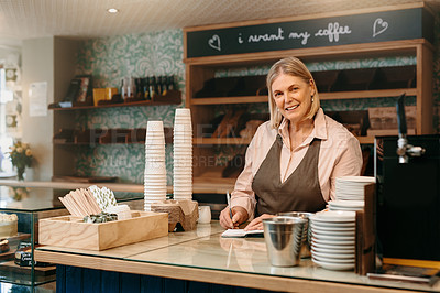 Buy stock photo Cropped portrait of a mature female entrepreneur writing down orders while standing in her self-owned coffee shop