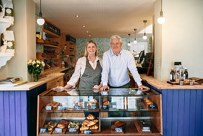 Buy stock photo Cropped portrait of a mature couple standing behind the counter of their self-owned coffee shop