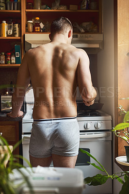 Buy stock photo Rearview shot of an unrecognizable shirtless man cooking in the kitchen at home