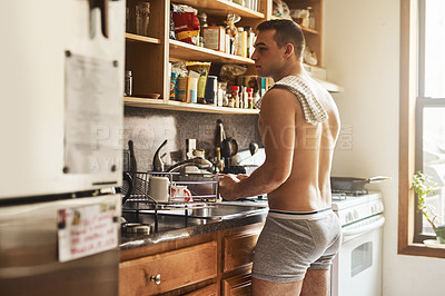 Buy stock photo Cropped shot of a handsome young shirtless man washing dishes in the kitchen at home
