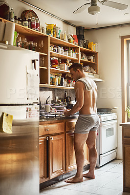 Buy stock photo Shot of a handsome young shirtless man washing dishes in the kitchen at home