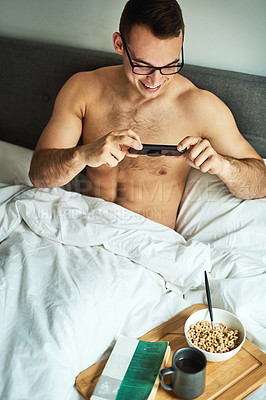 Buy stock photo Cropped shot of a handsome young shirtless man taking a picture of his breakfast in bed at home