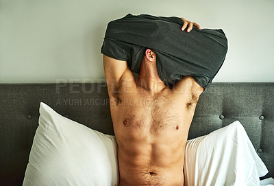 Buy stock photo Cropped shot of an unrecognizable man undressing on his bed at home