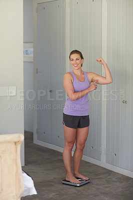 Buy stock photo Shot of a young attractive woman weighing herself on a scale at home