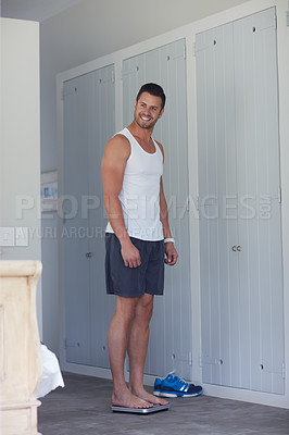 Buy stock photo Shot of a young handsome man weighing himself on a scale at home