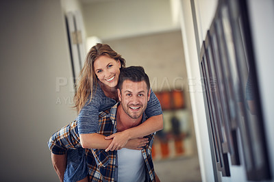 Buy stock photo Cropped shot of a young handsome man giving his beautiful wife a piggyback ride at home